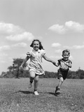 1940s Two Smiling Children Running Holding Hands in Grassy Field Photographic Print