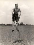 1930s-1940s Smiling Happy Boy Wearing Striped Shirt and Short Pants Walking on Pair of Stilts Photographic Print