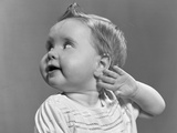 1940s-1950s Close-Up Portrait of Baby Girl with Curl on Top of Head with Hand Held Up Beside Ear Photographic Print