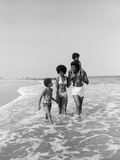 1970s African American Family Wading in Surf Walking Along Beach Together Photographic Print