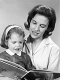 1960s Woman Reading Story Book to Girl Child Photographic Print