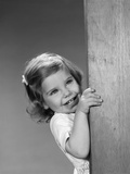 1960s Child Little Girl Smiling Peeking around Corner Photographie