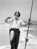 1920s-1930s Smiling Woman Standing in Ocean Surf Wearing Rubber Waders Holding Fishing Rod Photographic Print