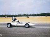 1960s Race Car Driver in Lotus Ford Car Taking Victory Lap Holding Checkered Flag Photographic Print