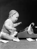 1960s Side View of Chubby Baby Seated Behind Adding Machine with Pencil Behind Ear Photographic Print