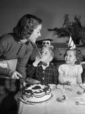 1950s Woman Mother Cutting Birthday Cake for Two Children Sitting at Table Wearing Party Hats Photographic Print