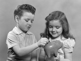 1950s Boy and Girl Putting Money into Piggy Bank Photographic Print