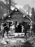 1920s-1930s Couple in Front of Log Cabin Standing by Horses with Saddles Both Wearing Jodhpurs Photographic Print