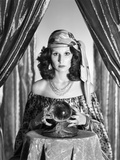 1970s Gypsy Woman Between Sparkly Curtains with Hands around Crystal Ball Staring into Camera Photographic Print