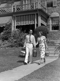 1930s Couple Walking Out of House Down Sidewalk Carrying Picnic Baskets and Thermos Jug Photographic Print