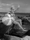 1960s Smiling Blond Teenage Girl Sitting on Rocky Shore Holding a Beach Ball Waving Photographic Print