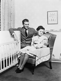 1930s-1940s Mother Sitting in Chair in Nursery Baby 11 Months on Lap Drinking from Bottle Photographic Print