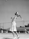 1930s Woman Playing Tennis About to Hit Ball with Racket Fotografiskt tryck