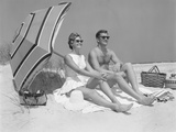 1960s Couple in Sunglasses Sitting on Beach Blanket with Legs Extended with Umbrella Photographic Print