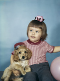 1950s-1960s Little Girl in Party Hat Sitting Holding a Cocker Spaniel Puppy Photographic Print