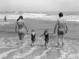 1970s Family on Vacation at Ocean Beach Holding Hands Walking on Sand in Surf Photographic Print