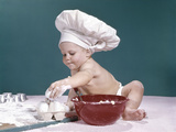 1960s Baby Wearing Chefs Hat Holding Egg Surrounded by Cooking Equipment Photographic Print