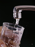 1970s Hand Holding Glass under Faucet Filling with Drinking Water Photographic Print
