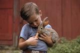 Boy Feeding a Rabbit Reproduction photographique par William P. Gottlieb
