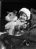 1920s-1930s Little Girl Sitting in Toy Car Steering with Dog Photographic Print