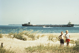 1950s Young Boy and Girl on Beach Smiling with a Tanker Ship on Lake Photographic Print by G. Knapp