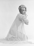 1960s Profile Portrait of Blond Woman in Sheer Nightgown Kneeling Down with Hands Pressed Together Photographic Print