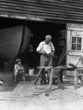 1920s-1930s Elderly Man Working at Saw Horses as Little Boy Watches Hull of Boat Photographic Print