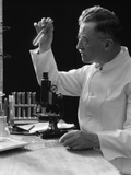 1920s-1940s Scientist Lab Technician in White Coat Looking at Test-Tube in Front of Microscope Photographic Print
