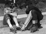 1950s Teen Boy Helping Girl Put on Metal Roller Skates Sitting on Sidewalk Photographic Print
