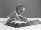 1960s Baby Wearing Glasses Looking for a Word in Big Dictionary Photographic Print