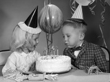 1960s Boy Blowing Out Candles on Birthday Cake Reproduction photographique