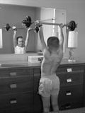Boy Exercising with Dumbbell at Mirror in Bedroom Photographic Print by B. Taylor