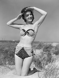 1950s Smiling Young Woman Kneeling in Grassy Sand Wearing Polka Dot Bikini Shading Eyes from Sun Photographic Print