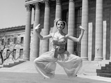 1960s Woman in Middle Eastern Belly Dance Costume Jumping in Front of Building Photographic Print