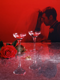 1960s Champagne Flutes with Rose and Wedding Rings in Red Filter with Couple in Background Photographic Print