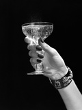 1930s-1950s Woman Hand Ornate Metal Bracelet Holding Up New Year Toast Glass of Champagne Reproduction photographique