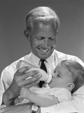 1960s Smiling Blond Father Feeding Child Milk in Glass Baby Bottle Photographic Print