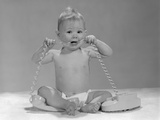 1960s Blond Baby Sitting Up Chewing on Telephone Cord Photographic Print
