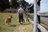 Boy and His Dog Walking Along a Fence Reproduction photographique par William P. Gottlieb