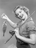 1950s Smiling Woman with a Fishing Rod over Her Shoulder Holding Up a Fish Photographic Print