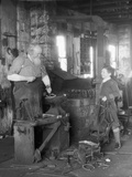 1930s Elderly Blacksmith with Hammer at Anvil as Young Boy Holding Harness Looks on Smiling Photographic Print