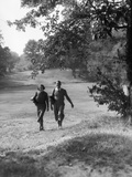 1930s Couple Man Woman Each Carrying a Golf Bag Walking Down the Fairway of the Golf Course Photographie