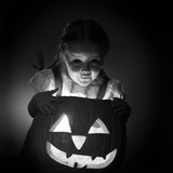1950s Little Girl Standing over Carved Pumpkin Face Lit by Candle Photographic Print