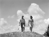 1930s Couple Man Woman Golfers Walking Together over Crest of Hill Carrying Clubs Photographic Print