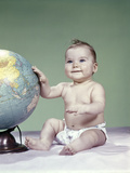 1960s Smiling Baby Girl Sitting in Diapers Hand Touching World Globe Photographic Print