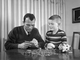 1960s Father Son with Piggy Bank Counting Money Coins Photographic Print