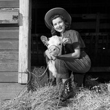 Girl Posing with Calf in Straw Filled Stall in Barn Lámina fotográfica por B. Taylor