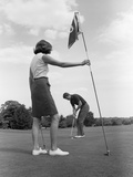 1970s Couple Playing Golf Man Putting Woman Holding Flag Photographic Print