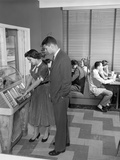 1950s Teen Couple Playing Juke Box in Malt Shop with Other Teens in Booths Photographie