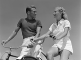 1930s-1940s Smiling Blonde Couple on Bikes Looking at One Another Photographic Print